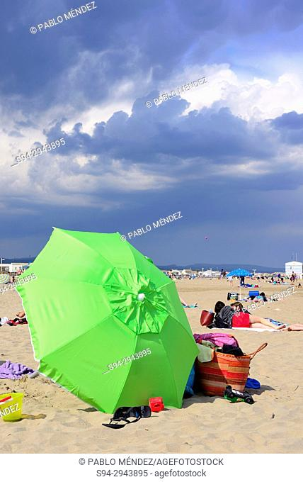 Green umbrella waiting for a storm in Gruissan beach, Languedoc-Roussillon, France