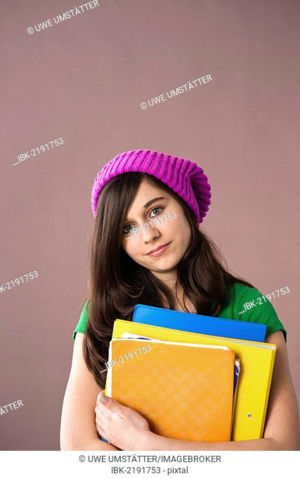 Girl with long hair wearing a hat and holding her school books in her arms