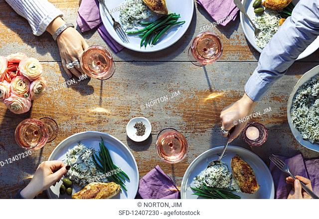 A table scene with chicken, rice, olives, green beans and wine
