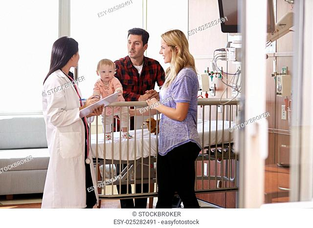 Pediatrician Visiting Parents And Child In Hospital Bed
