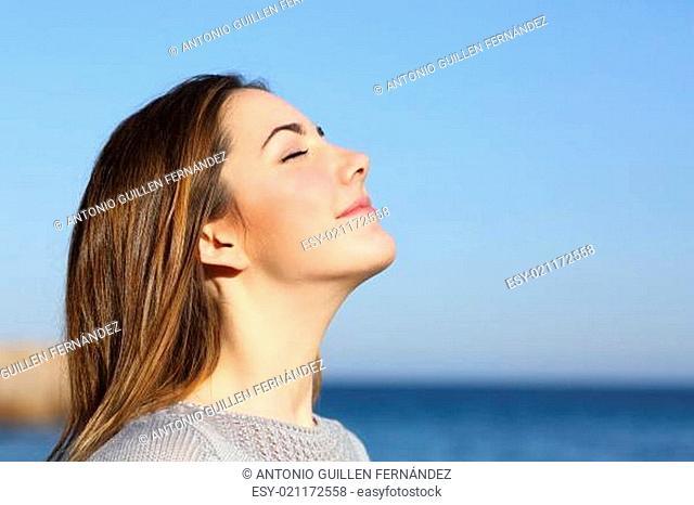 Woman portrait breathing deep fresh air on the beach