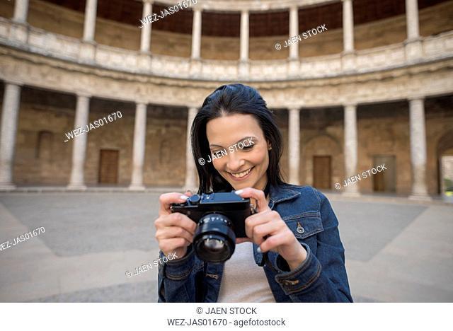 Spain, Granada, smiling young woman looking at camera at the Alhambra