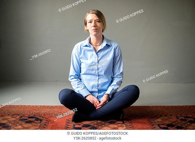 Tilburg, Netherlands. Studio shot of an attractive, blonde woman sitting on carpet
