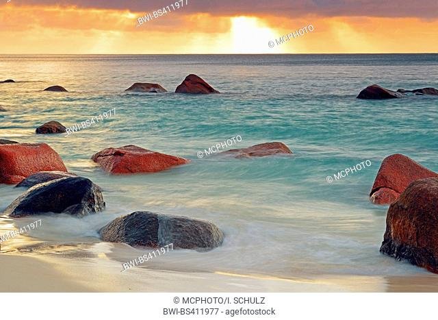 granite rocks in the waves of Anse Lazio at sunset, Seychelles, Praslin