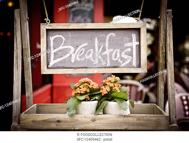 A 'breakfast' sign with flowers on a wooden rack in a restaurant