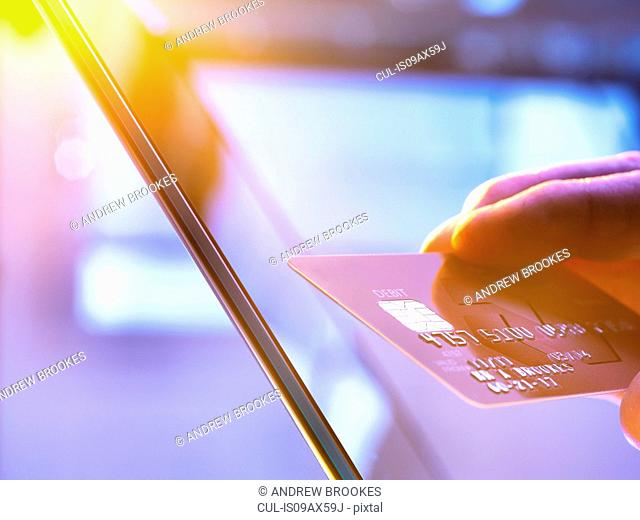 Man using his credit card online for shopping and banking with sunlight coming through window