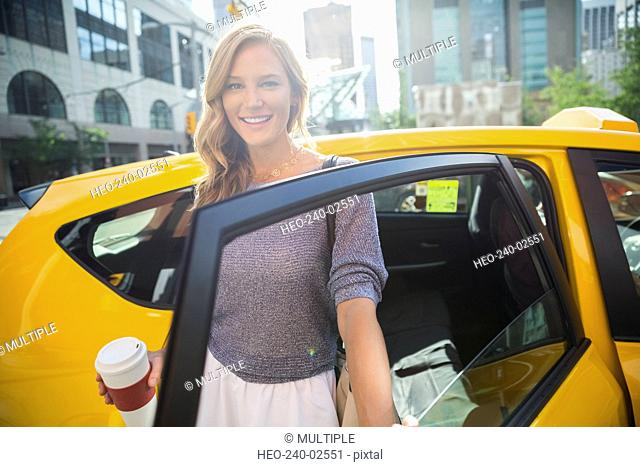 Portrait smiling businesswoman with coffee getting out taxi