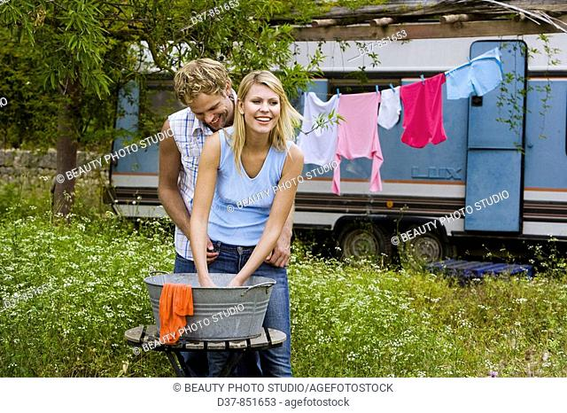 Couple doing the washing with affection outdoors