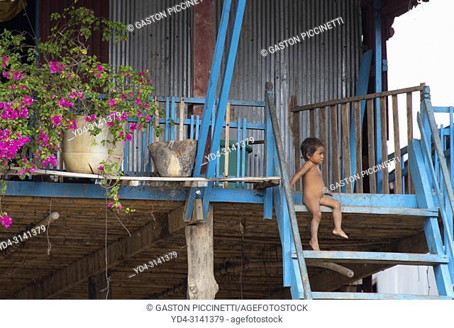 Girl sitting on the stairs of her house, floating village of Kompong Phluk, Siem reap Province, Kingdon of Cambodia. Kompong Phluk