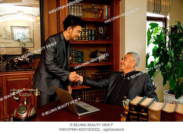 Two men shaking hands in study