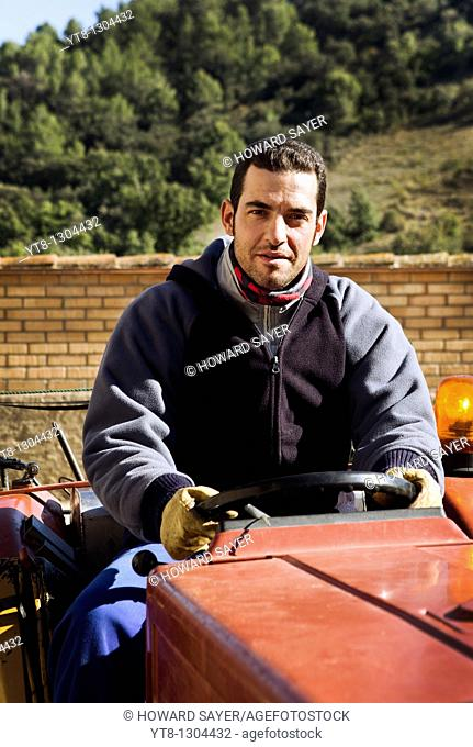 Spanish male farm worker at the steering wheel of a tractor