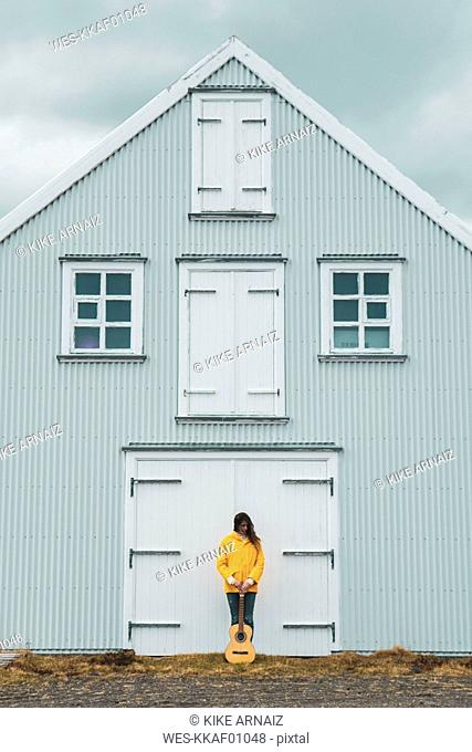 Iceland, woman with guitar standing at house