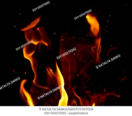 bright orange and yellow flames with sparks, close up, black background