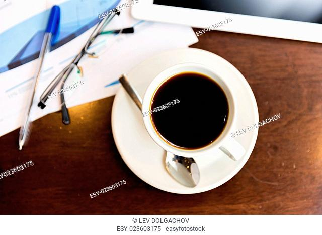 business and drinks concept - close up of coffee cup, charts and tablet pc on table