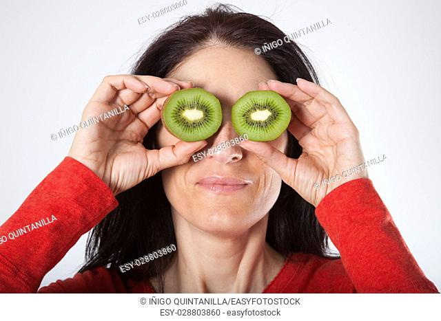 face portrait of adult brunette woman with red sweater holding two halves of open kiwi on her eyes