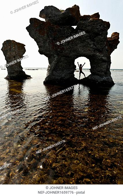 Child playing in natural arch of sea rock