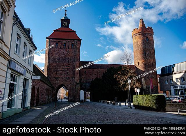 04 November 2020, Brandenburg, Bernau: The square in front of the stone gate with the city wall Hungerturm (r)in Bernau is deserted