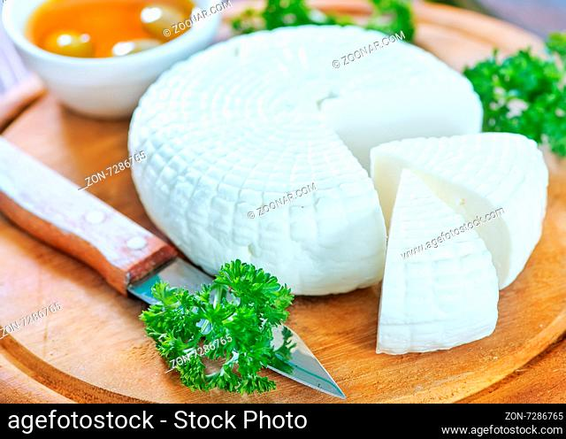 round cheese and aroma spice on wooden board