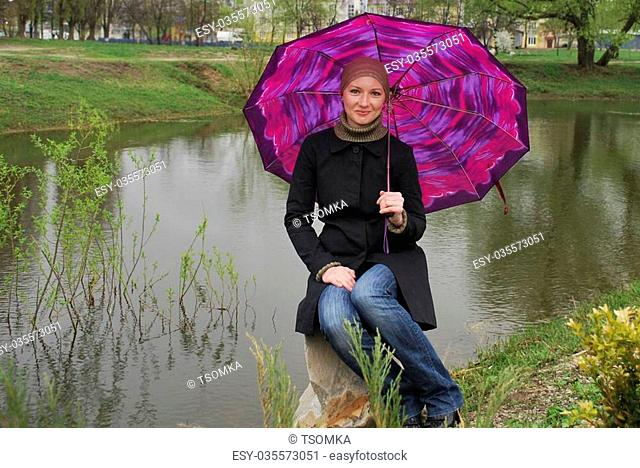 Near lake spring sits on a rock girl with umbrella