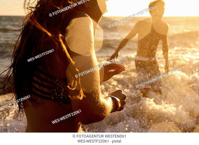Playful couple in the sea at sunset