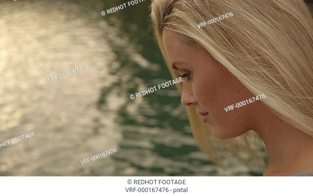 Close up of blond woman's face as she sits beside water, Marbella region, Spain