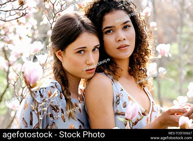 Loving sisters standing in park during springtime