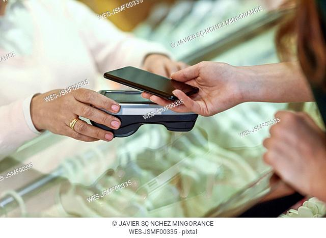 Close-up of woman paying with smartphone in a store