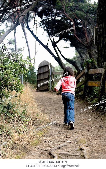 Rear view of girl (6-7) walking dirt road
