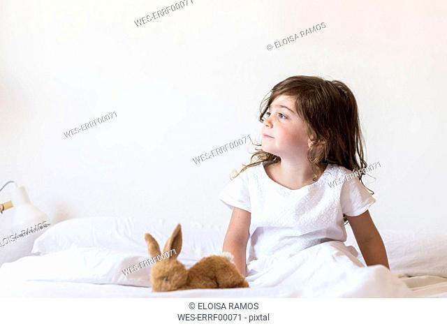 Little girl sitting on bed looking away