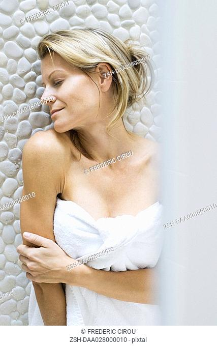 Woman wrapped in towel, leaning chin on shoulder, smiling, eyes closed