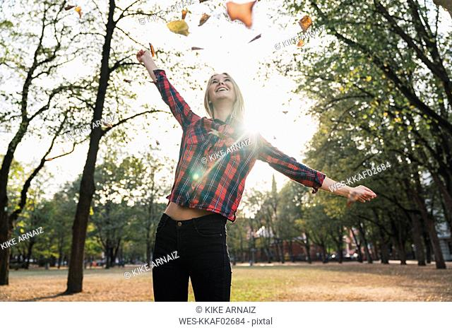 Happy young woman throwing autumn leaves in the air