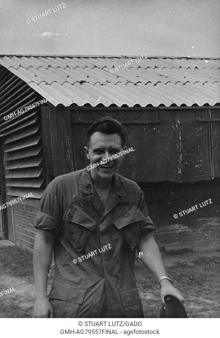 A candid photograph of a soldier laughing while looking directly at the camera, Vietnam, 1967