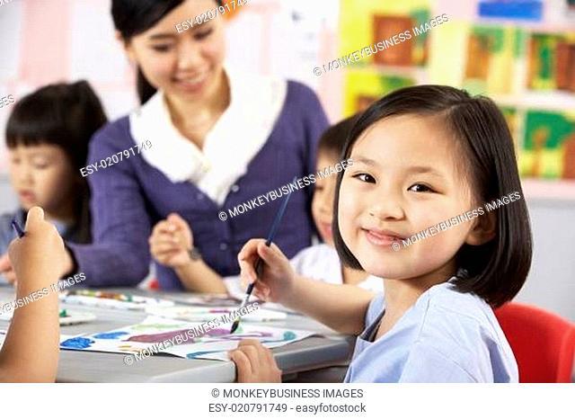 Female Pupil Enjoying Art Class In Chinese School Classroom