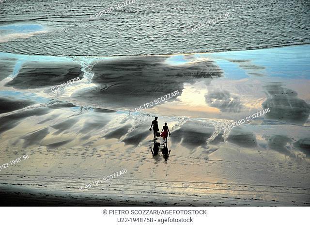 Jericoacoara, Ceará, Brazil, couple walking along the seashore at sunset
