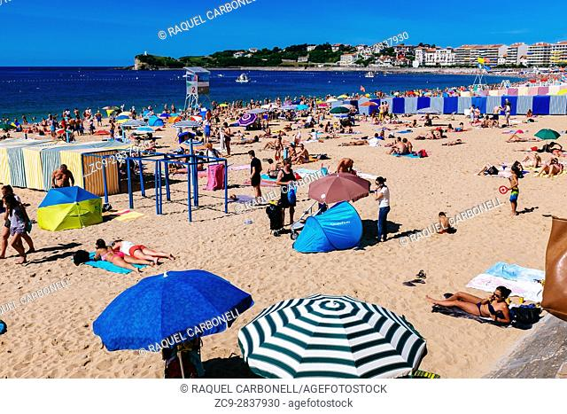 Tourists sunbathing on beach during summer, Jean de Luz, Basque Country, France
