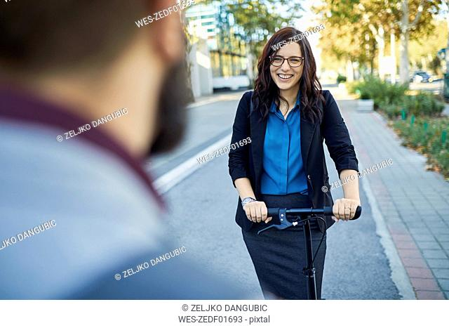 Smling businesswoman with scooter meeting businessman