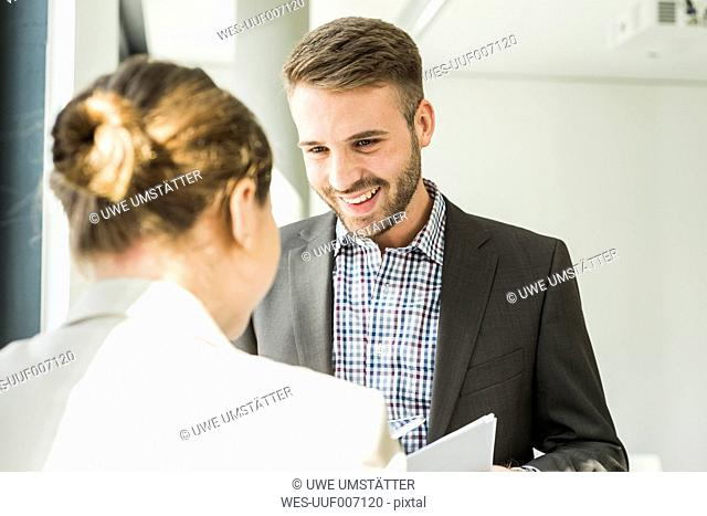 Smiling young man looking at colleague in office