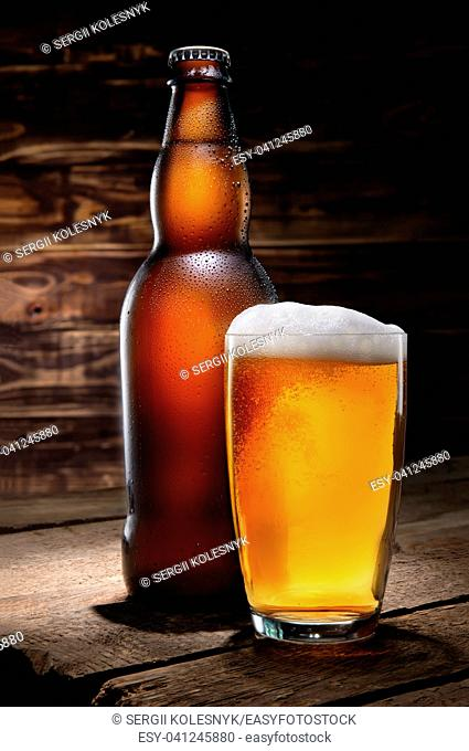Beer in glass and bottle on wooden background