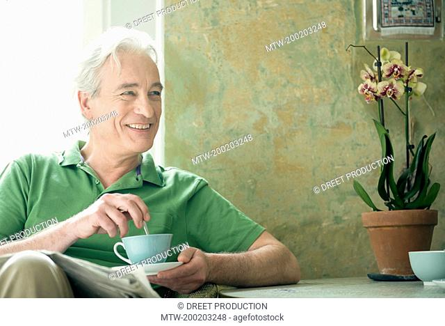 Mature man holding coffee cup, smiling
