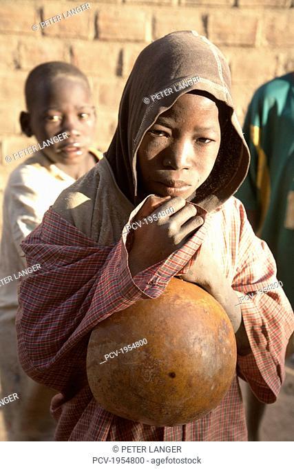Boy holding pumpkin in Djenne, Mali