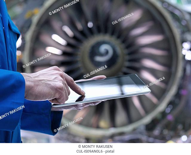 Engineer using digital tablet in front of jet engine in aircraft maintenance factory