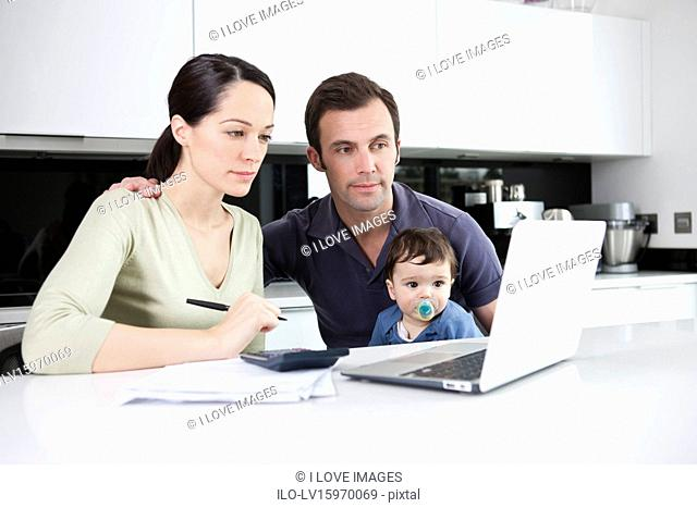 A couple and their baby son looking at their household finances online
