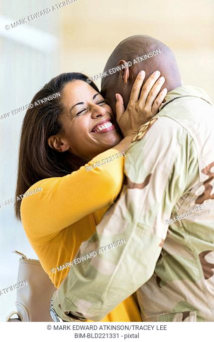 African American soldier hugging wife