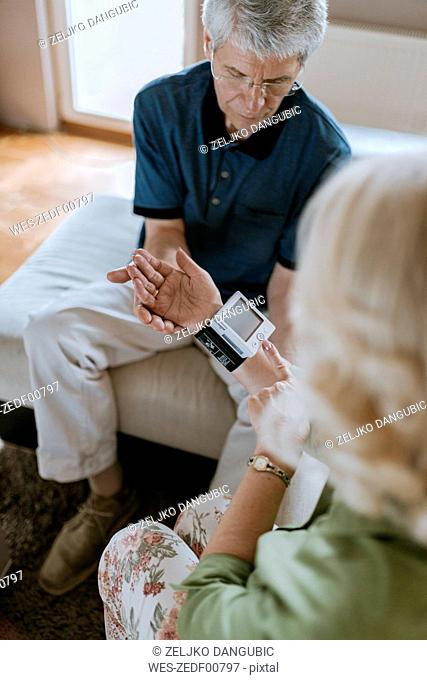 Senior couple taking blood pressure at home