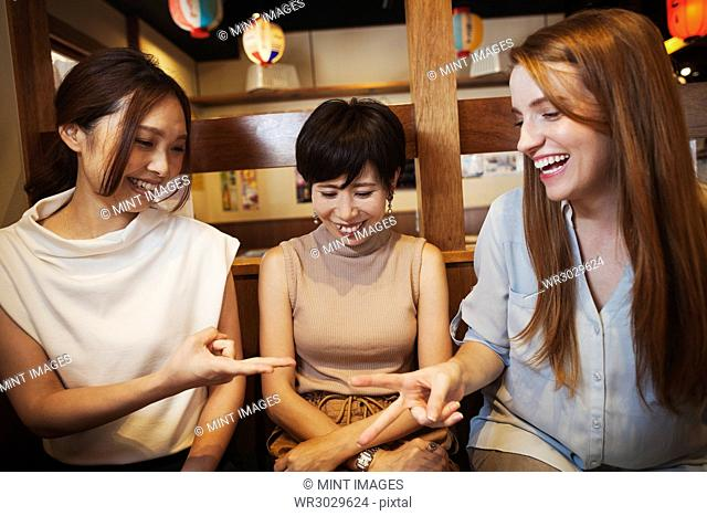 Three women sitting side by side in a restaurant, holding chopsticks