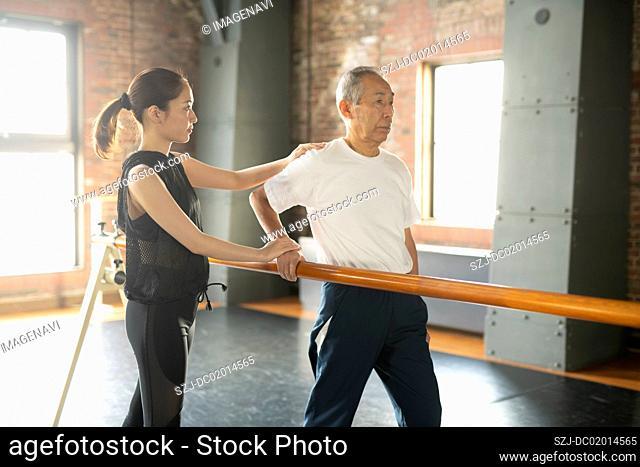 Senior man undergoing rehabilitation walking exercises with trainer