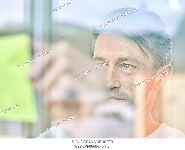 Businessman looking at sticky note at glass pane
