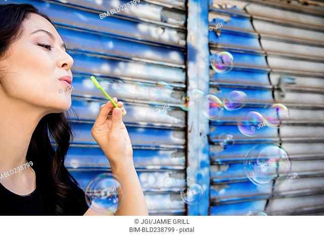 Thai woman blowing bubbles in city