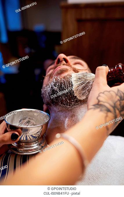 Woman applying shaving cream to man's beard
