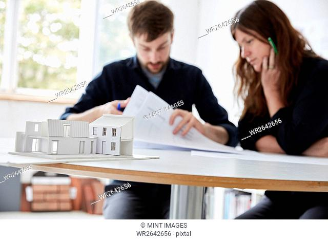 A modern office. Two people at a meeting discussing plans and architectural drawings. A small-scale model building in the foreground